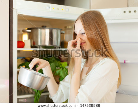 stock-photo-long-haired-woman-holding-her-nose-because-of-bad-smell-near-fridge-at-home-147529586