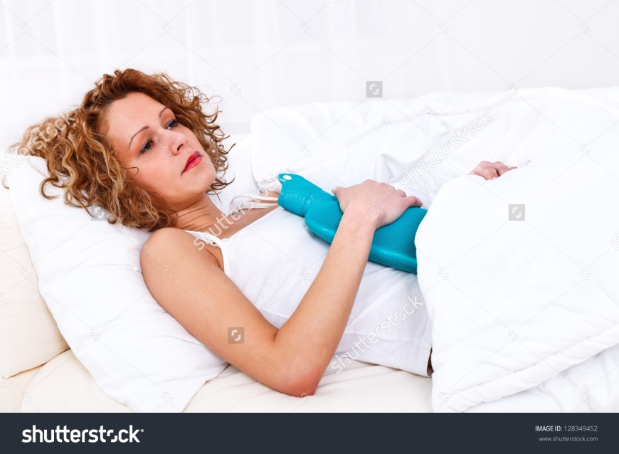 stock-photo-beautiful-sick-woman-in-bed-having-a-hot-water-bottle-on-belly-128349452